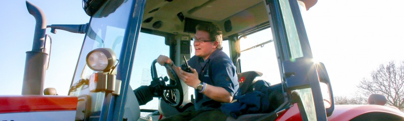 Farmer in a tractor using a radio to communicate